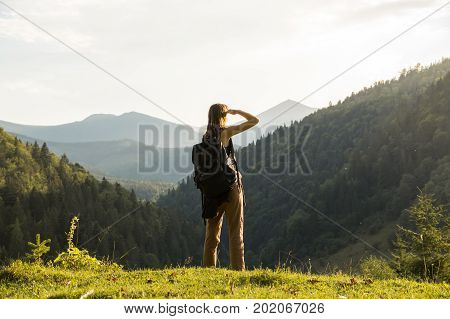 Young female backpacker stands top of the hill at sunset. Tourist hiker girl enjoys stunning view of sunset in mountains. Tourist hiker girl enjoys stunning view of sunset in mountains