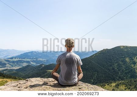 Back of skinny male person sitting in lotus position top of rock in ukrainian carpathian mountains. Young tourist enjoys gorgeous landscape scenery on hot sunny day