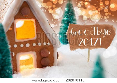 Gingerbread House In Snowy Scenery As Christmas Decoration. Christmas Trees And Candlelight. Bronze And Orange Background With Bokeh Effect. English Text Goodbye 2017 For Happy New Year