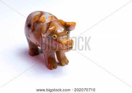 Closeup of a figurine of a pig standing on a white table