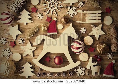 Flat Lay With Many Christmas Decoration, Like Rocking Horse, Ball, Sleigh, Fir Cone And Tree. Vintage Rustic Wooden Background With Instagram Filter And Frame