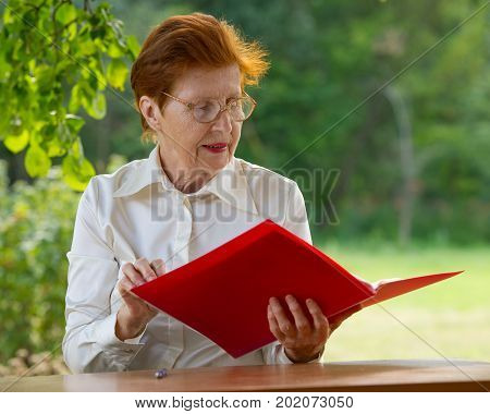 A woman of a businesswoman in age looks at documents. Age eighty years. Portrait of a woman wearing glasses outdoors.