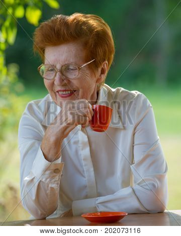 smiling woman in glasses is drinking coffee outdoors. Age eighty years.