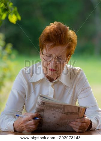 woman in glasses is watching a magazine outdoors. Age eighty years.