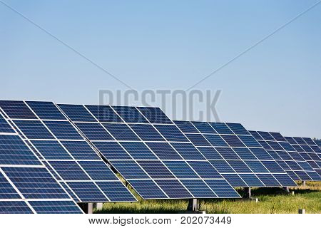 Solar panels energy farm on sky background. Photovoltaic modules producing clean electric power. Alternative energy systems and environmental problems concept, copy space