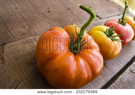 Natural tomatoes without medication and without hormones, delicious village tomatoes, nice tomatoes on a wooden floor in a plate