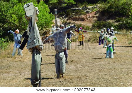 Scarecrow dolls. Numerous scarecrows placed in a field simulating a dance.