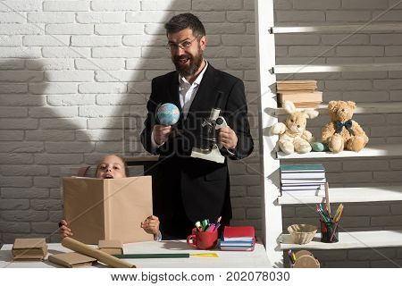 Schoolgirl and tutor with happy faces hold open book globe and microscope. Home education concept. Kid and man by desk with school supplies. Girl and teacher in classroom on white brick background