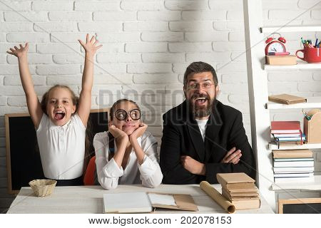 Girls and bearded man sit at desk with books. Kid older sister and their tutor with happy faces. Home schooling and back to school concept. Teacher and schoolgirls on classroom background