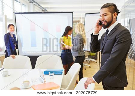 Businessman on the phone in conference room during meeting