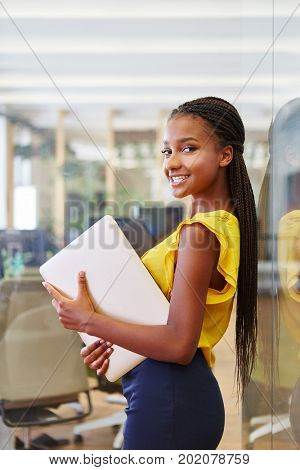 Young student in her business trainee program holding computer