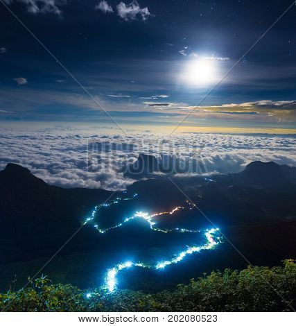 Illuminated path to the top of the mountain of Adam Peak with moon and stars in the sky. View from Adam Peak, Sri Lanka