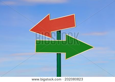 Road signpost with two blank copy space arrows green and red directing to different directions left and right over clear blue sky low angle side view