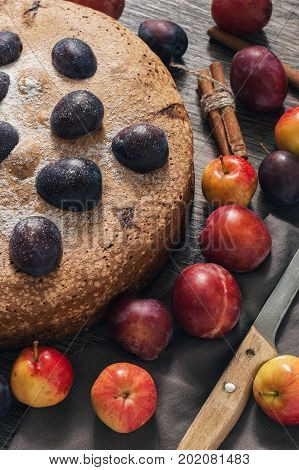 Pie with fruit. The cake is decorated with fresh plums and apples