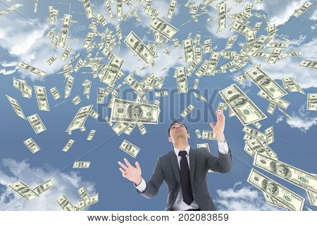 Digital composite of Business man looking at money rain against sky with clouds
