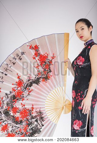 Digital composite of Geisha and giant fan against white background