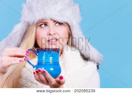 Accessories and clothes for cold days fashion concept. Blonde woman in winter warm furry hat drinking hot drink from mug. Blue background.