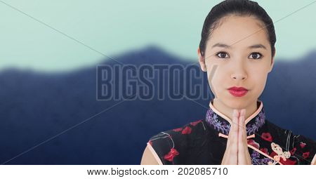 Digital composite of Close up of geisha hands together against blurry mountain