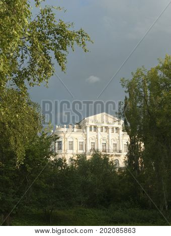 Sunlit three-story old mansion of the XIX century in classical style behind the trees against the backdrop of a stormy sky