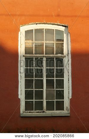 Fragment of a bright red wall with an vintage dusty window with a white wooden frame
