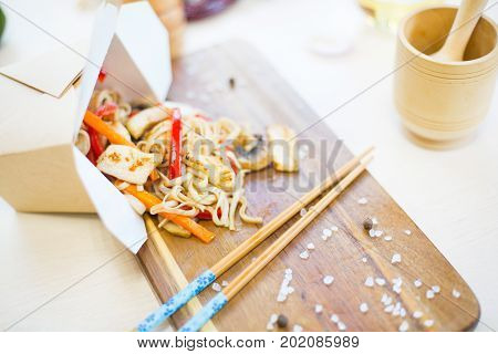 Noodles With Mushroom And Chicken In Take-out Box On Wooden Table. Stir Fry Noodle With Chicken In A