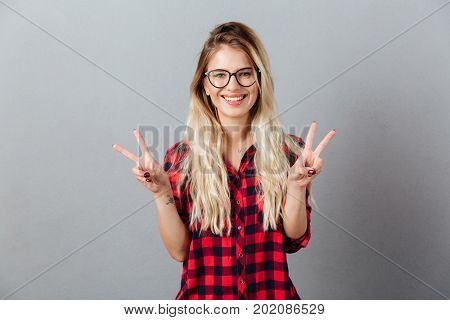 Image of cheerful young blonde woman wearing glasses standing isolated over grey wall showing peace gesture. Looking at camera.