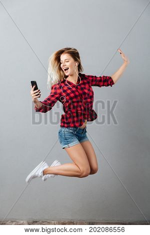 Photo of happy young blonde woman jumping isolated over grey wall. Looking aside listening music by phone.