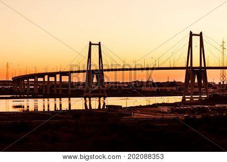 Sunset silhouette of the large suspension concrete bridge near Figueira da Foz Portugal
