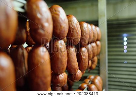 mouthwatering smoked sausages on the background of a meat factory or butcher shop