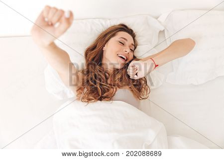 Top view of young sleepy woman in pajamas stretching in bed in the morning