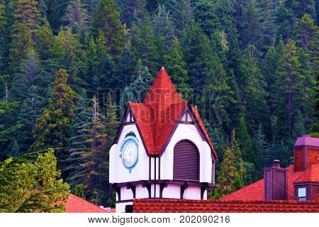 August 29, 2017 in Lake Arrowhead, CA:  Lake Arrowhead Village Clock Tower overlooking the outdoor mall surrounded by a pine forest where tourists can shop and dine at a rustic mountainous setting taken in Lake Arrowhead, CA