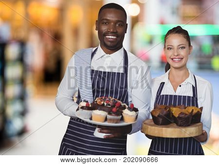 Digital composite of Restaurant owners with cakes against blurry background