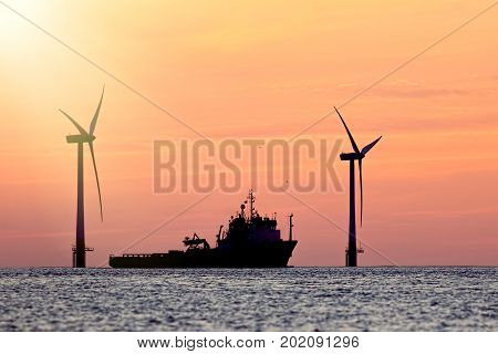 Sustainable resources. Wind farm with ship silhouette at tropical sunrise or sunset. Solar and wind energy and food supply represented in this tranquil image with copy space.