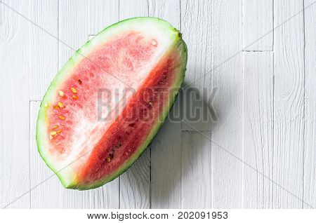 A quarter of a watermelon on white wood background top view. Piece of fresh watermelon on white table with empty space for text. Blank background