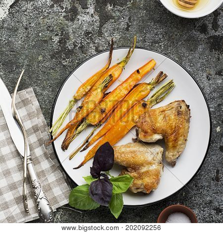 Baked carrots in honey glaze with garlic, olive oil, sage and garlic with chicken wings for lunch with basil leaves of green and purple. Top View