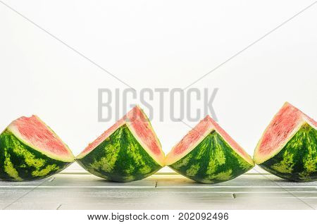 Four slices of a watermelon lie in a row on white wooden table on white background. Minimalistic blank background