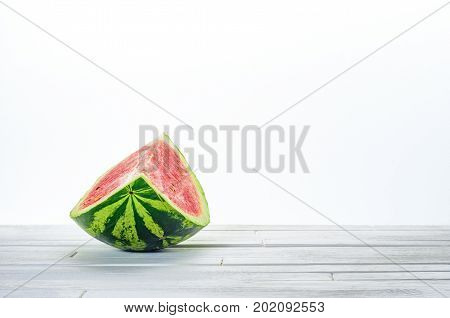Slice of a watermelon on white wooden table on white background. Minimalistic blank background