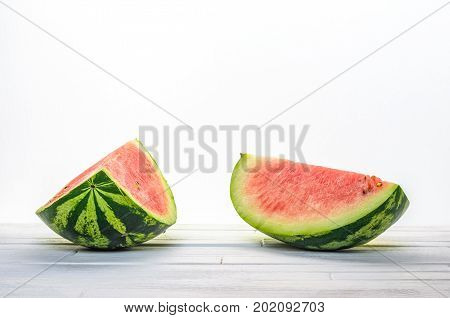 Two pieces of a watermelon on white wooden table on white background background front view. Blank minimalistic background