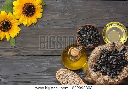 Sunflower Oil In Glass Jug , Seeds And Flower On Dark Grey Wooden Background. Top View With Copy Spa