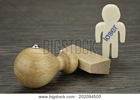 The wooden man is prejudiced and stamped as loser