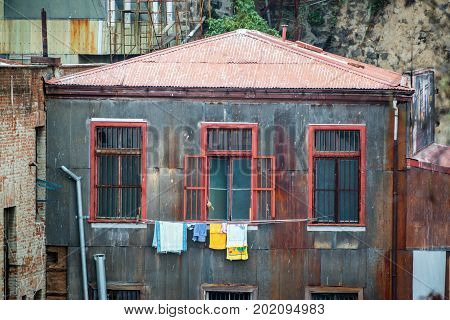 Old rusty building with hanging laundry in Valparaiso Chile