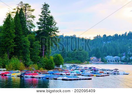 August 29, 2017 in Lake Arrowhead, CA:  Yachts and boat rentals at docks surrounded by a pine forest taken in Lake Arrowhead, CA where locals can ride their yachts on the lake and tourists can rent boats to ride on the lake taken in Lake Arrowhead, CA