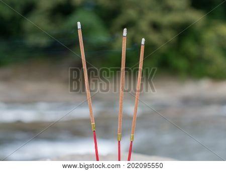 Three Buddhist Burning Incense Sticks On A River.