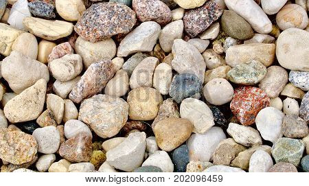 Multicolored coarse rounded stones as a background