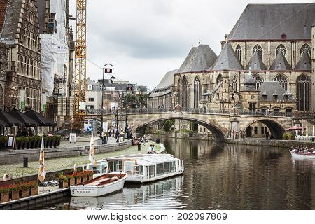 GHENT BELGIUM - JUNE 22 2016: Picture of a canal in Sint-Michielsbrug with a boat houses sidewalk a crane people and the Sint Michielskerk Church in cloudy day in Ghent.