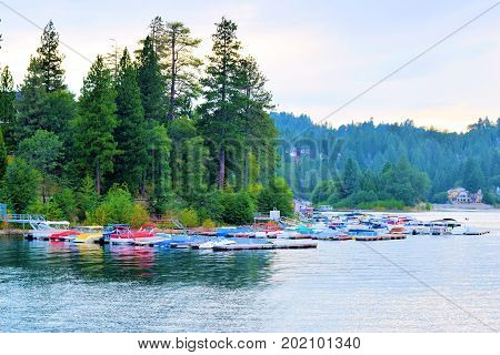 August 29, 2017 in Lake Arrowhead, CA:  Yachts and boats tied to docks taken at the Lake Arrowhead Marina where people can ride their yachts and tourists can rent and ride boats on the lake surrounded by a pine forest taken in Lake Arrowhead, CA