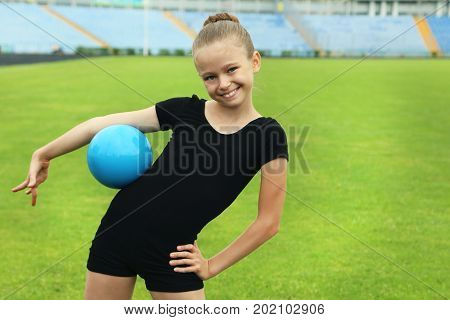 Young girl gymnast with the blue ball