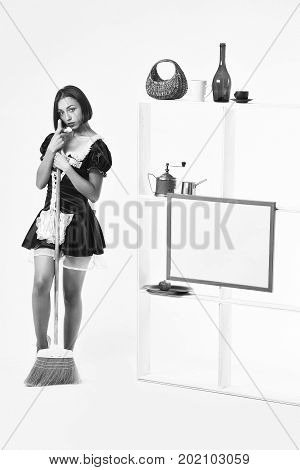 girl in sexy maid servant costume posing with sweep broom near kitchenware on shelves isolated on white background black and white