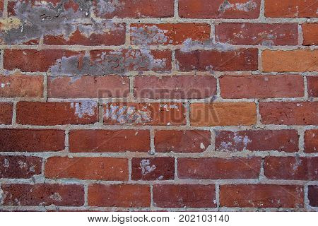Old, weathered brick background that has been patched in several places.