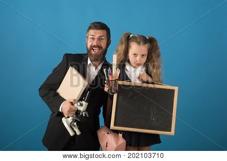 Father And Schoolgirl With Happy And Grumpy Faces On Blue